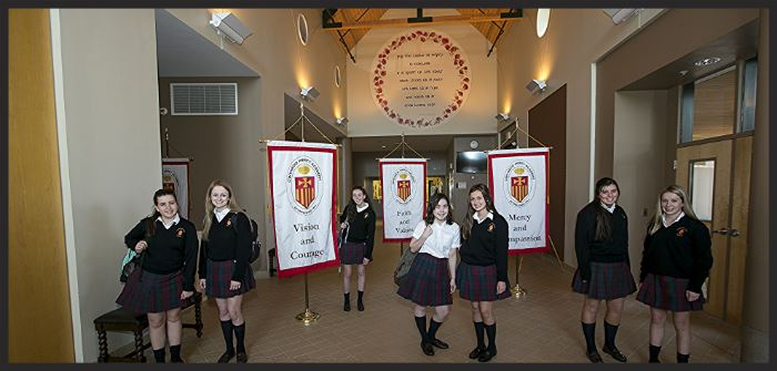six students in the foyer of the school next to school banners