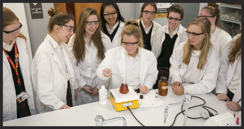 chemistry lab students wearing lab coats and goggles doing an experiment