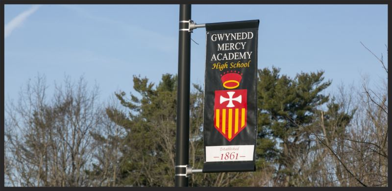 School Banner with crest hanging on a pole outside the school