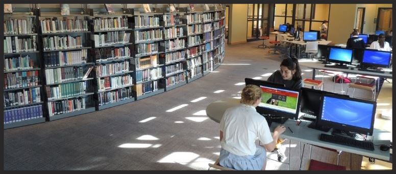 Learning Commons area with bookshelves and two students at computers